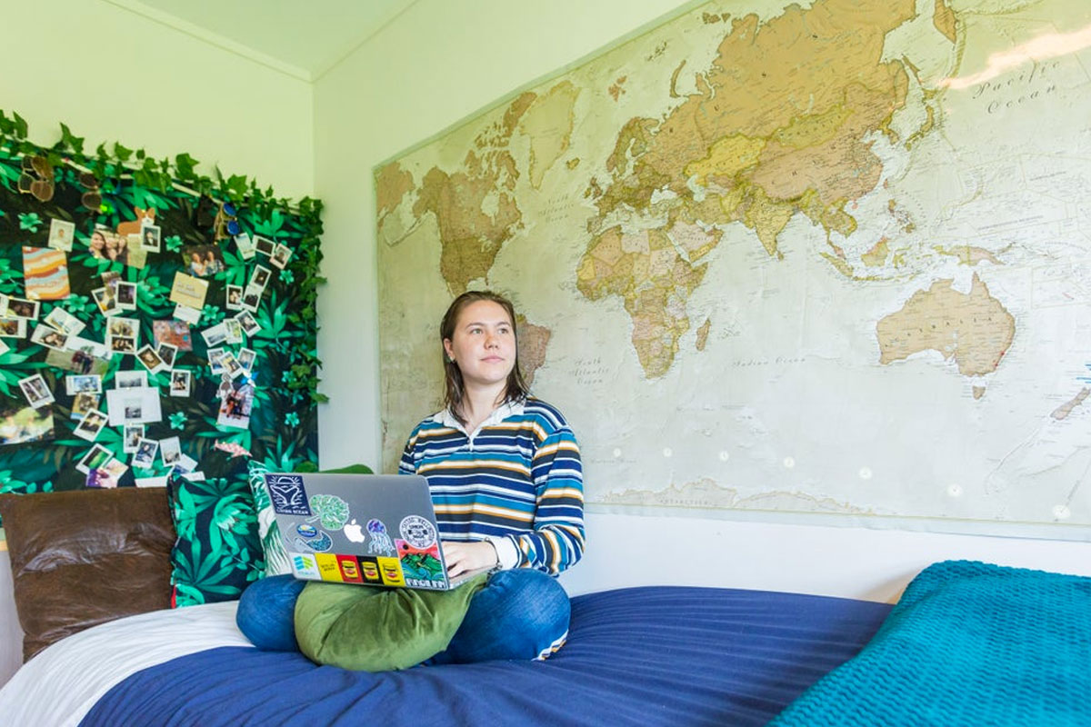 Student sitting on bed